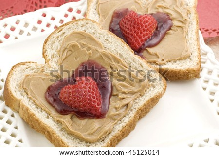 Two slices of honey wheat toast with peanut butter and strawberry jam in a heart shape, topped with a heart shaped strawberry,  selective focus, horizontal closeup with copy space - stock photo