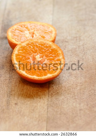 Two slices of juicy orange clementines on wooden chopping board. - stock photo
