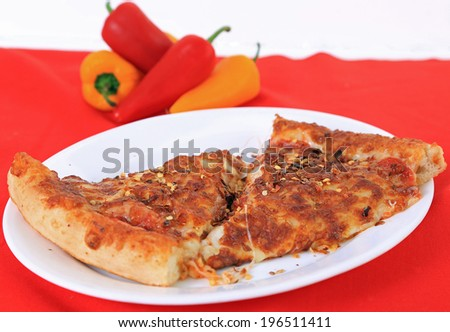 Two slices of leftover pepperoni pizza sprinkled with crushed red pepper on white plate against red background with colorful hot peppers.  Shallow depth of field with copy space. - stock photo
