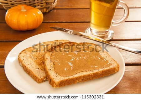 Two slices of multigrain toast with almond butter and tea