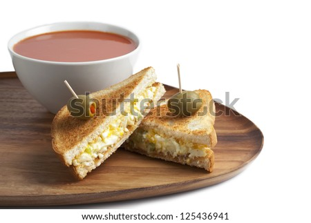 Two slices of toast bread with egg salad on stick with olives, Tomato soup on the side - stock photo