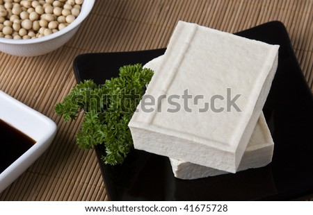 Two slices of tofu cheese on a black dish. - stock photo