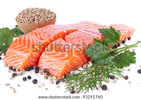 two slices trout fillet with spices on white background