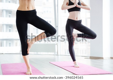 Two slim young women doing balancing pose on pink yoga mat - stock photo
