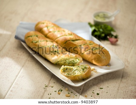 two small baguettes filled with herb butter on white plate - stock photo