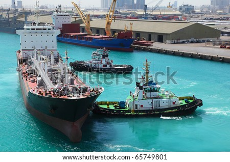 Two small boats docked to industrial ship in port at sunny day - stock photo
