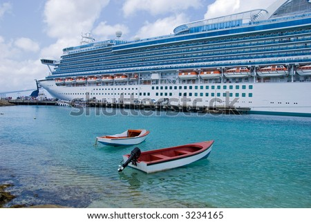 Two small boats lie in front of a large cruise ship - stock photo