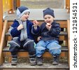 Two small boys, brothers sitting on the steps in a children playground and eating apples. - stock photo