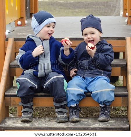 Two small boys, brothers sitting on the steps in a children playground and eating apples.
