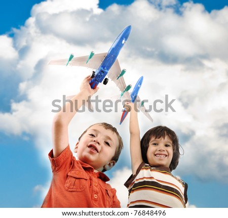 Two small boys with airplains in hands, idea for traveling around the World - stock photo
