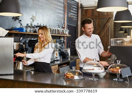 Two small business owner working in coffee shop prepaing coffee - stock photo