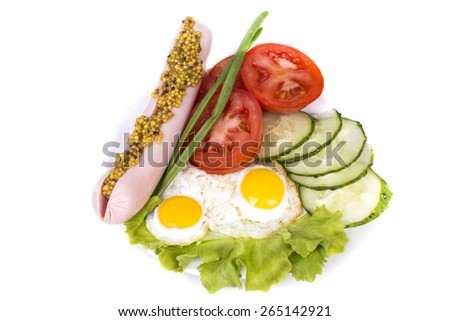 two small dietary fried eggs with vegetables and sausage with mu - stock photo