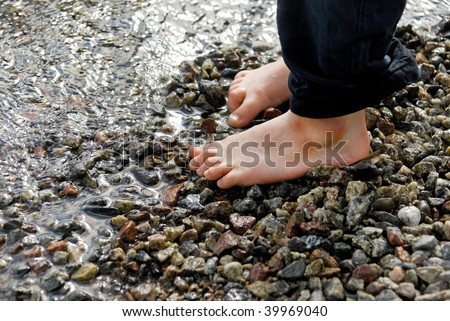 Two small feet on pebbles on the beach - stock photo