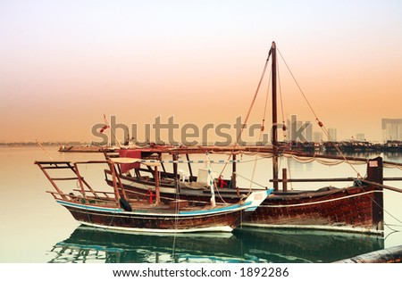 Two small fishing dhows of different types tied up in Doha harbour at dawn. The main post office and high-rise buildings of the New District are visible behind the row of boats opposite. - stock photo