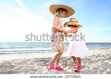 Two small girls dancing at the sunny beach. Shoot against the sun. - stock photo