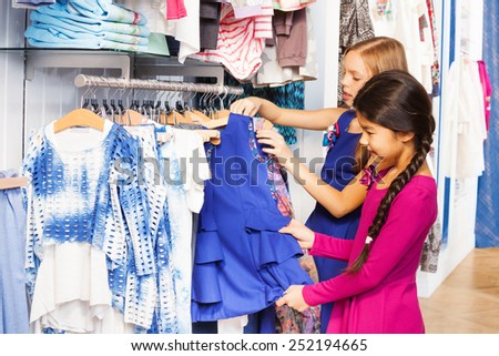Two small girls shop together in the clothes store - stock photo