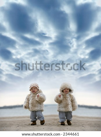 two small girls wearing her winter fur coat - stock photo