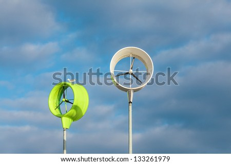 Two small green and white wind turbines against a blue cloudy sky - stock photo