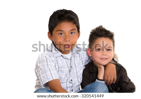 Two small hispanic boys sitting next to each other holding arms around like friends, white background.