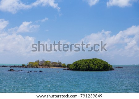 two small island in the middle of the ocean by a sunny day