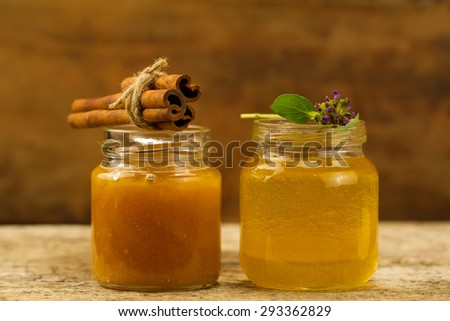 two small jars of fresh honey with cinnamon and flowers on wooden background - stock photo