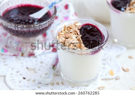 Two small jars with homemade yogurt with blackcurrant jam and granola (sunflower seeds, corn, oat and barley flakes and nuts), selective focus - stock photo