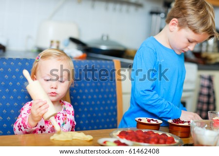 Two small kids helping in kitchen to bake pie - stock photo