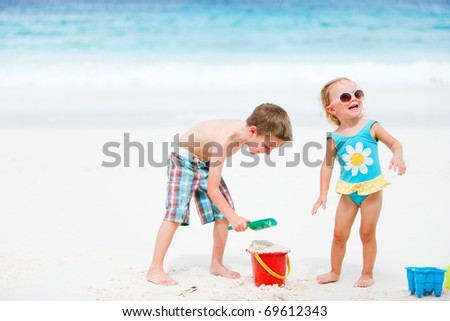 Two small kids playing with beach toys at seashore - stock photo