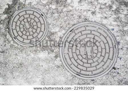 Two Small Plastic Gray Round Sewer Lids on The Concrete Ground. One Is Larger, The Other Is Smaller.