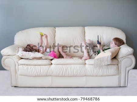 Two small pre-kindergarten aged children, a boy and a girl are lying on the sofa in the house playing hand held computer games.