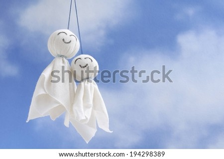 Two small white ghost shapes on a sting. - stock photo