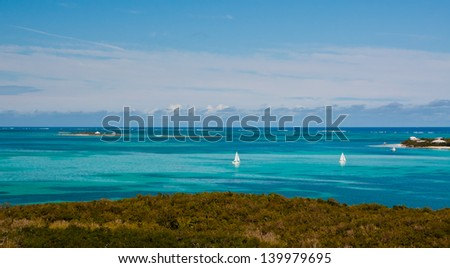 Two small white sailboats in the crystal clear blue and turquoise waters of the bahamas - stock photo