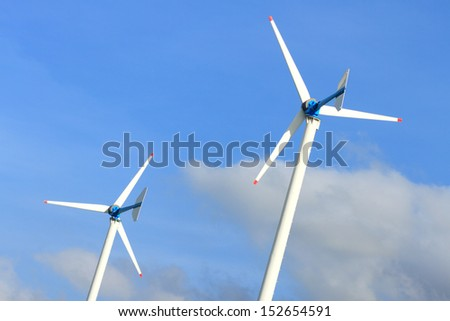 Two small wind turbines on blue sky with cloud as background