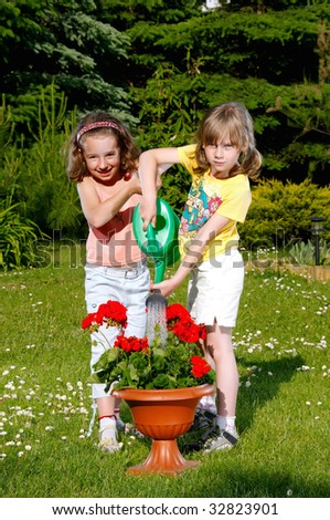 Two small young girls water the flower