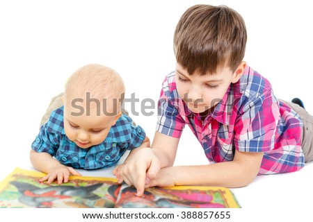 Two Smart children little baby boys in shirt reading a book on the floor, isolated on white background - stock photo