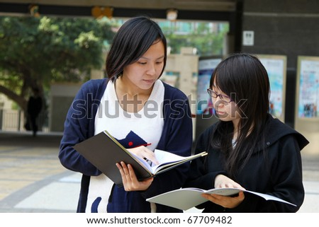 Two smart Chinese University students discussing on campus