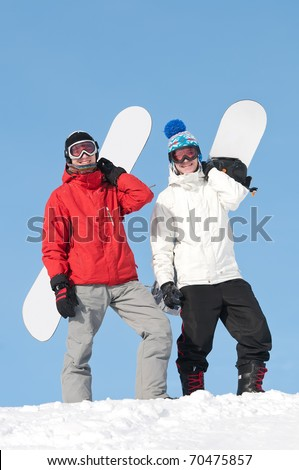 two smiley happy sportsman with snowboards at winter outdoor - stock photo