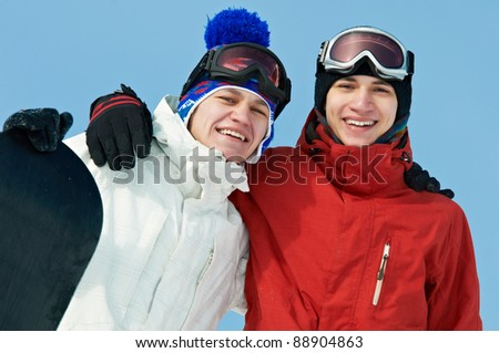 two smiley happy sportsman with snowboards at winter outdoor