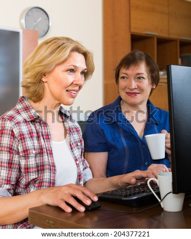Two smiling aged females looking at PC screen with cup of tea in hands  - stock photo