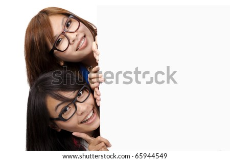 Two Smiling and Beautiful Girls  behind the  white board - stock photo