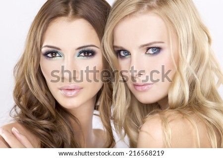 Two smiling attractive and sensuality young adult girl friends - blond and brunette on white background - stock photo