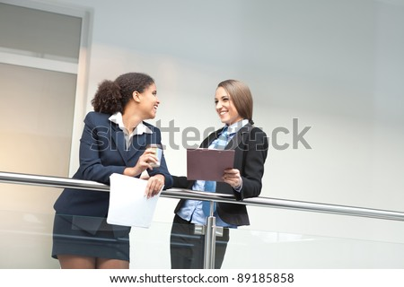 Two smiling attractive young businesswomen chatting on coffee break, indoor