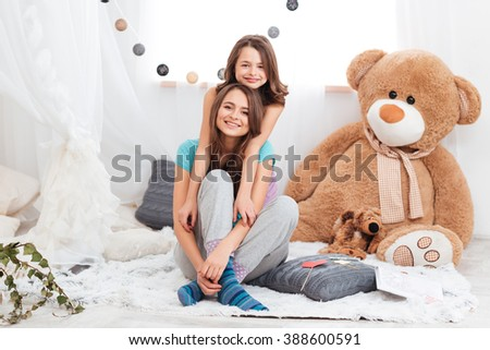 Two smiling beautiful sisters sitting together in children room - stock photo
