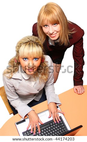 Two smiling business lady at the computer isolated on white. - stock photo