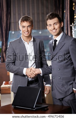 Two smiling business men shake hands each other at a meeting at restaurant - stock photo