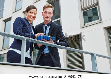 Two smiling business people working with tablet computer in city - stock photo