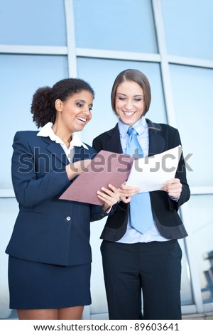 two smiling businesswomen discussion about  job