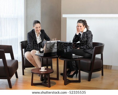 Two smiling businesswomen sitting in front of laptops - stock photo