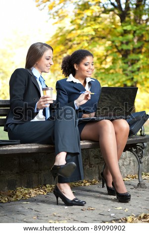 two smiling businesswomen working on coffee break in park - stock photo