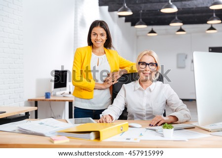 Two smiling businesswomen working together on the computer at the table in office and looking at camera - stock photo